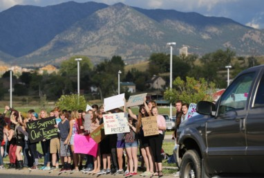 Students protest outside of Ralston Valley High School, as a motorist passes by, Tuesday, Sept. 23, 2014, in Arvada, Colo. The students are protesting a proposal by the Jefferson County School Board to emphasize patriotism and downplay civil unrest in the teaching of U.S. history. (AP Photo/Brennan Linsley)