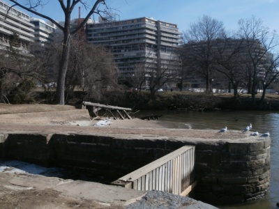 A view of the Watergate Complex from the entrance to the C&O Canal. The tidewater lock is in the foreground, while the former site of the dam lies just behind the ruined timbers in the middle of the photo..